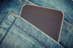 Vintage photo, Mobile phone with blank screen in pocket jeans, smartphone Stock Image
