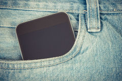 Vintage photo, Mobile phone with blank screen in pocket jeans, smartphone Stock Photography