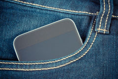 Vintage photo, Mobile phone with blank screen in pocket jeans, smartphone Royalty Free Stock Photography