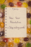Vintage photo, New years resolutions written in notebook and colorful candies Royalty Free Stock Image