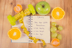 Vintage photo, New years resolutions written in notebook and dumbbells with centimeter Royalty Free Stock Photo