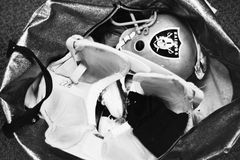 Vintage photo of Oakland Raiders Equipment bag. Vintage b&w shot into an Oakland Raiders equipment bag featuring a helmet and pads. (Image taken from B&W Stock Image