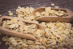 Vintage photo, Oat flakes with spoon on wooden background Royalty Free Stock Photo