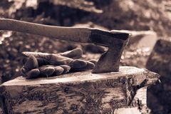 Vintage photo of an old axe and work gloves Royalty Free Stock Photos