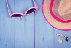Vintage photo, Pink sunglasses and straw hat on blue wooden boards, accessories for summer Stock Image