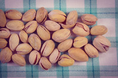 Vintage photo, Pistachio nuts on checkered tablecloth, healthy eating Royalty Free Stock Image