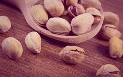 Vintage photo, Pistachio nuts with spoon on wooden table, healthy eating Royalty Free Stock Photos