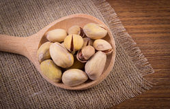 Vintage photo, Pistachio nuts with spoon on wooden table, healthy eating Stock Photo