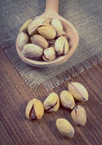 Vintage photo, Pistachio nuts with spoon on wooden table, healthy eating Royalty Free Stock Image