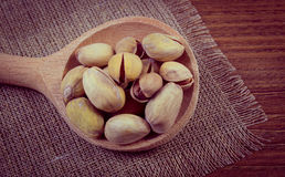 Vintage photo, Pistachio nuts with spoon on wooden table, healthy eating Stock Photography