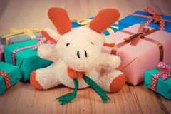 Vintage photo, Plush reindeer with colorful gifts for Christmas or other celebration Royalty Free Stock Photo