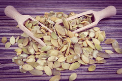 Vintage photo, Pumpkin seeds with spoon on wooden background Royalty Free Stock Photography