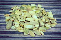 Vintage photo, Pumpkin seeds on wooden background Royalty Free Stock Images