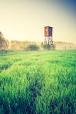 Vintage photo of raised hide on foggy meadow Stock Photography