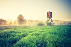 Vintage photo of raised hide on foggy meadow Stock Image