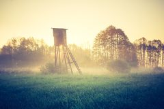 Vintage photo of raised hide on foggy meadow Stock Photos