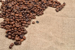 Vintage photo, roasted coffee beans on brown jute background. Mo. Rning pleasure. Still life. Selective focus. Copy space Stock Image