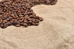 Vintage photo, roasted coffee beans on brown jute background. Mo. Rning pleasure. Still life. Selective focus. Copy space Stock Photo