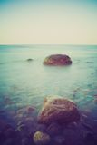 Vintage photo of rocky sea shore at sunset Stock Photo