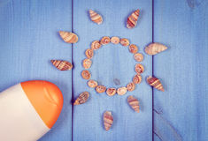 Vintage photo, Seashells in shape of sun and sun lotion on boards, accessories for summer Stock Photos