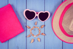 Vintage photo, Seashells in shape of sun, sunglasses, straw hat and towel on blue boards, accessories for summer Stock Images
