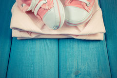 Vintage photo, Shoes and bodysuits for newborn, concept of expecting for baby, copy space for text Royalty Free Stock Image