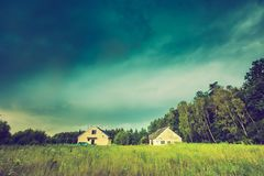 Vintage photo of storm sky over meadow, house and forest Stock Photos