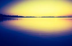 Vintage photo of sunset over calm lake Royalty Free Stock Photo