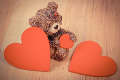 Vintage photo, Teddy bear with red heart on wooden surface, symbol of love Royalty Free Stock Image