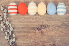 Vintage photo, Twigs of willow and colorful Easter eggs wrapped woolen string on rustic board, copy space for text Stock Photo