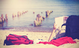 Vintage photo of unrecognizable person reading book. Vintage toned photo of unrecognizable person reading book on a beach Stock Photo
