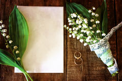Vintage photo Wedding bouquet of lilies of the valley and ring. Old shabby wooden painted background and a beautiful bouquet of fresh white flowers lily of the Royalty Free Stock Image
