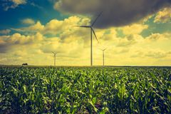 Vintage photo of windmills standing on corn field Royalty Free Stock Photography