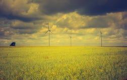 Vintage photo of windmills standing on corn field Stock Photos