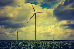 Vintage photo of windmills standing on corn field Royalty Free Stock Photos