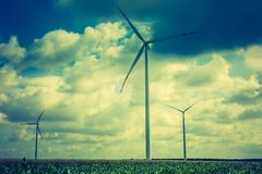 Vintage photo of windmills standing on corn field Stock Photo