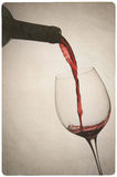 Vintage photo of wine and bottle. Old antique photo of red wine pouring into a glass Royalty Free Stock Photos