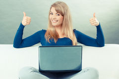 Vintage photo, Woman with laptop sitting on sofa and showing thumbs up Stock Photography