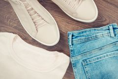 Vintage photo, womanly leather shoes, jeans pants and sweater on rustic boards. Vintage photo, womanly pink leather shoes, jeans pants and sweater lying on Stock Photos