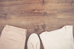 Vintage photo, womanly pink leather shoes, pants and sweater on rustic boards, copy space for text. Vintage photo, womanly pink leather shoes, pants and woolen Stock Image
