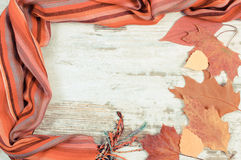 Vintage photo, Womanly woolen shawl and autumnal leaves with copy space for text, old rustic wooden background Stock Image