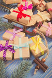 Vintage photo, Wooden sled and wrapped gifts with ribbons for Christmas, spruce branches Stock Photo