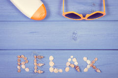 Vintage photo, Word relax made of seashells, sunglasses and sun lotion, summer time, copy space for text Stock Photography