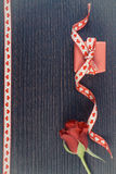 Vintage photo, Wrapped gift with red ribbon and rose for Valentines Day, copy space for text. Vintage photo, Wrapped gift with red ribbon and rose on wooden Royalty Free Stock Photo