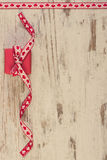 Vintage photo, Wrapped gift with red ribbon for Valentines Day, copy space for text. Vintage photo, Wrapped gift with red ribbon on old wooden background Stock Image