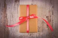 Vintage photo, Wrapped gift for Valentines day on old wooden table Stock Photography