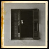 Vintage photograph of masked figure. By the broken windows of abandoned house Stock Image