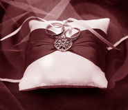 Vintage Photograph of wedding rings on white pillow with red ribbon Royalty Free Stock Images