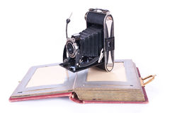 Vintage photography camera with old photoalbum. Over white Royalty Free Stock Image