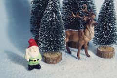 Vintage snowy forest firs gnome and reindeer blue Royalty Free Stock Image
